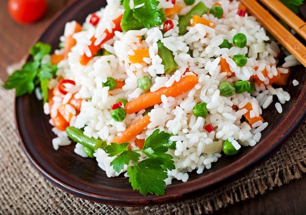 Riso sano appetitoso con le verdure in piatto bianco su una tavola di legno.