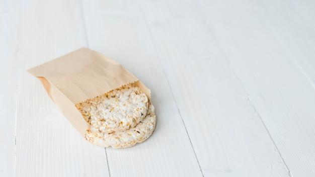 Riso soffiato croccante fatto in casa in sacchetto di carta marrone sullo scrittorio di legno bianco