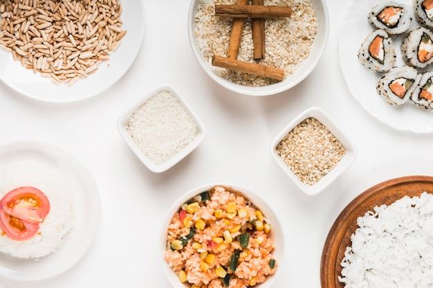 Riso soffiato; riso fritto cinese; riso crudo con bastoncini di cannella e sushi su sfondo bianco