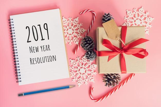 Risoluzione 2019 del nuovo anno, vista superiore marrone scatola regalo, notebook e decorazioni natalizie