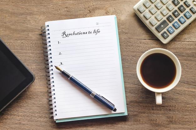Risoluzioni al testo di vita sulla nota di libro con la tazza di caffè, penna