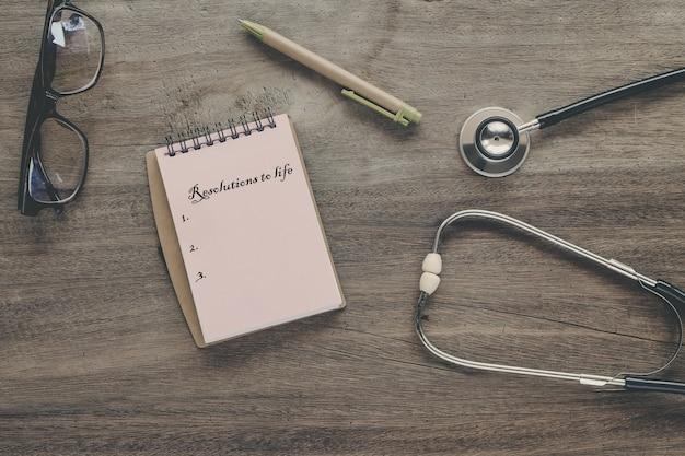 Risoluzioni al testo di vita sulla nota di libro con lo stetoscopio, penna.