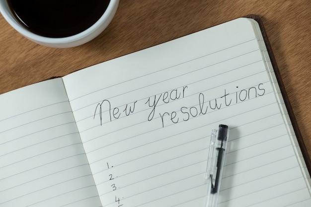 Risoluzioni del nuovo anno scritte sul diario con la tazza di caffè