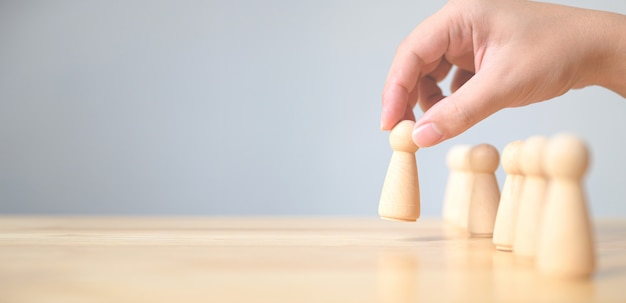 Risorse umane, gestione dei talenti, addetto all'assunzione, concetto di leader del team aziendale di successo. la mano sceglie un popolo di legno che si distingue dalla folla