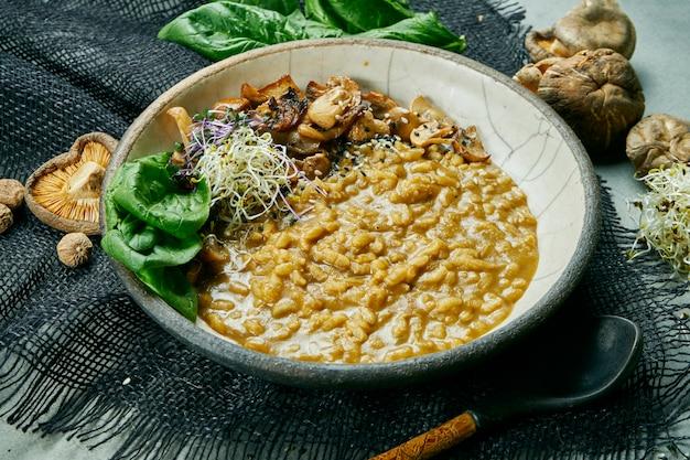 Risotto ai funghi vegetariano con microgreen e spinaci in una ciotola di ceramica su un panno grigio. cibo sano. vegano. cibo piatto