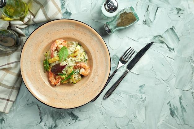 Risotto italiano con gamberetti e zucchine in un piatto di ceramica