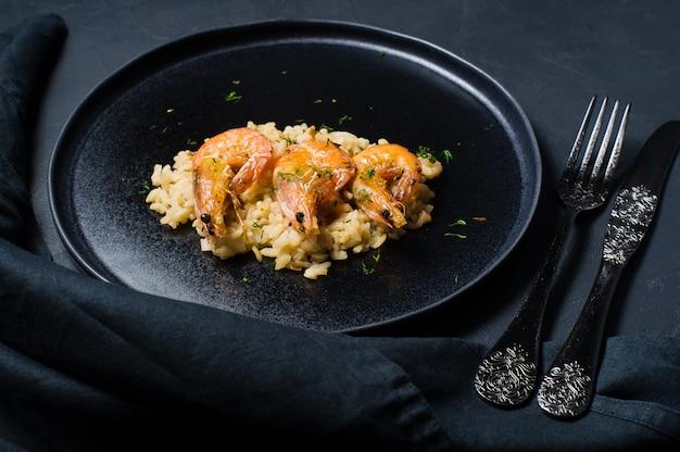 Risotto italiano con gamberi su un piatto nero.