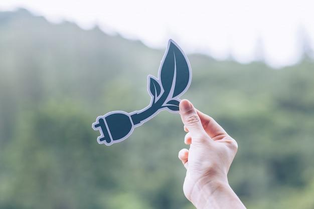 Risparmi la conservazione ambientale di concetto dell'ecologia del mondo con le mani che tengono la rappresentazione di carta tagliata della spina di corrente