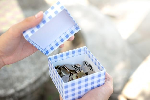 Risparmia il concetto dei soldi con le monete aperte della mano in scatola