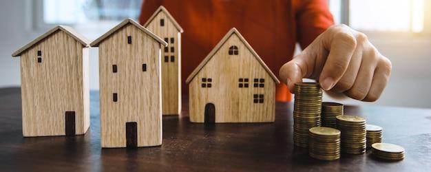 Risparmia sull'immobiliare, il proprietario ottiene il denaro per il concetto di casa, il modello di una piccola casa di legno sul tavolo con le monete impilate a mano da affittare o acquistare la residenza sopra menzionata con contanti all'agenzia bancaria