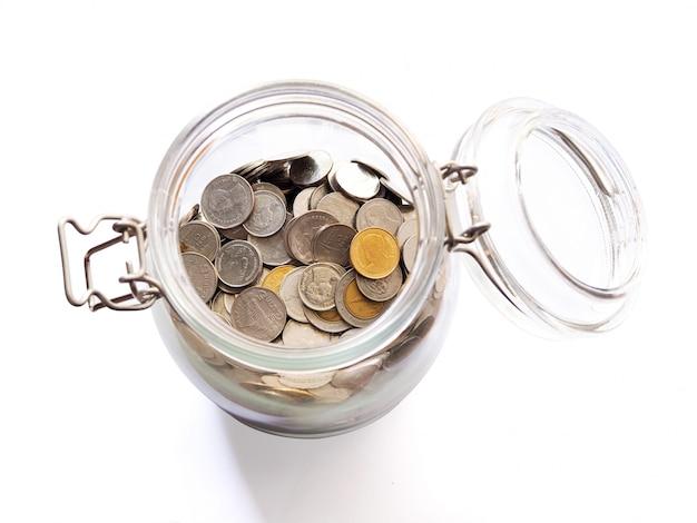Risparmio con la raccolta di monete, denaro tailandese in bottiglia di vetro per il futuro e gli investimenti.
