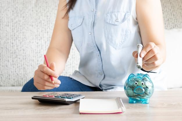 Risparmio di denaro concetto. donna che conta dollari al tavolo.