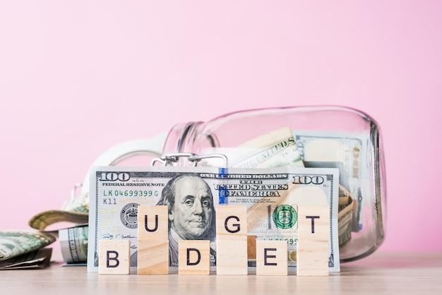 Risparmio di denaro e budget di pianificazione. banconote in dollari in cassa di risparmio di vetro e bilancio di parola su un rosa