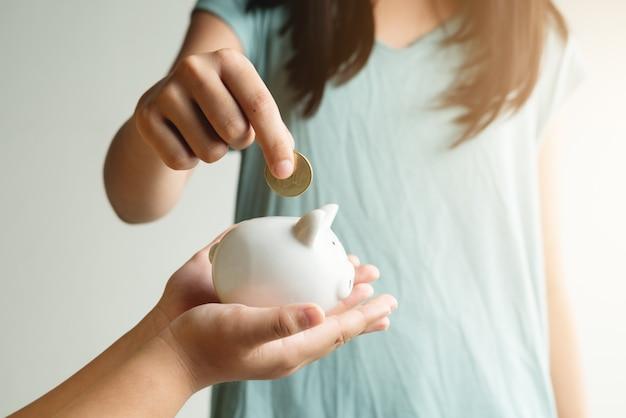 Risparmio e concetto di affari, due bambina con salvadanaio e monete a casa
