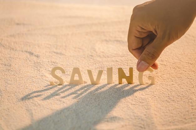 Risparmio in lettere di legno messe sulla spiaggia di sabbia