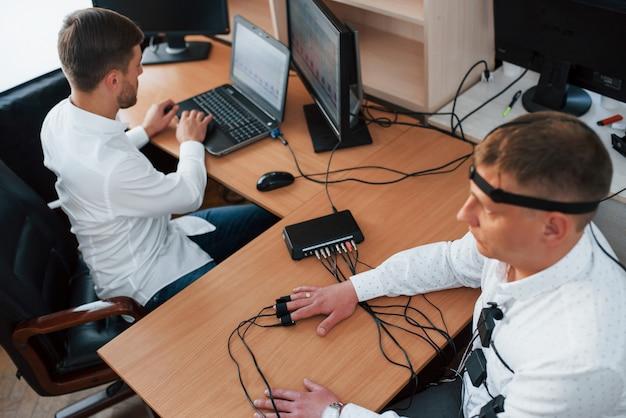 Rispondi velocemente. l'uomo sospettoso passa alla macchina della verità in ufficio. fare domande. test del poligrafo