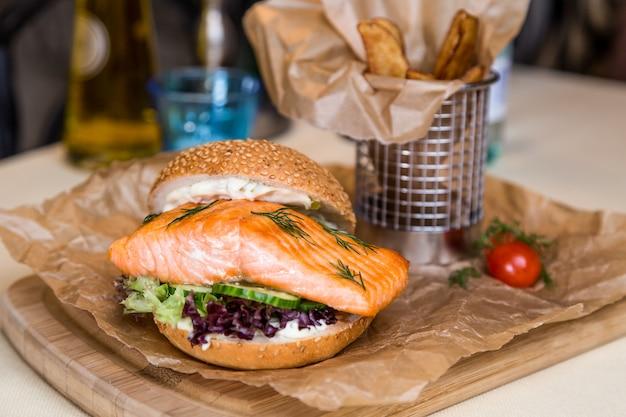Ristorante che serve piatto - hamburger con salmone, patate fritte su tavola di legno