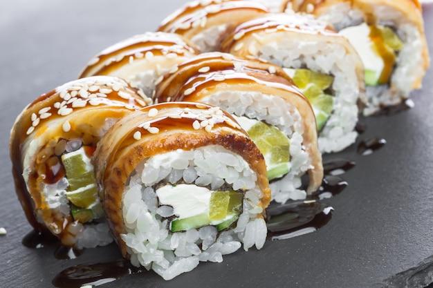 Ristorante giapponese, rotolo di sushi sul piatto di ardesia nera.