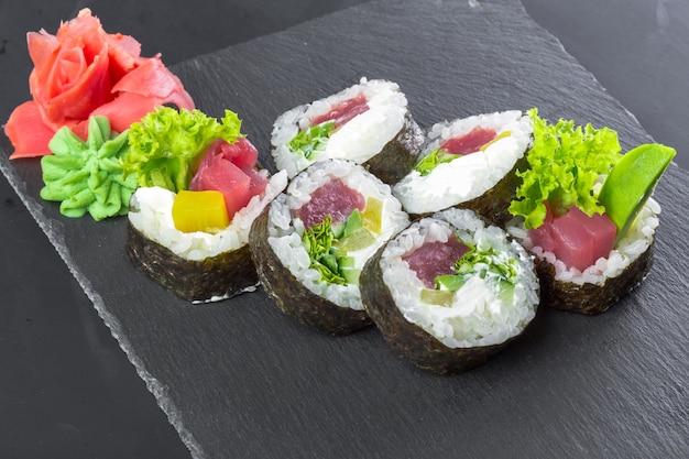 Ristorante giapponese, rotolo di sushi sul piatto nero dell'ardesia.