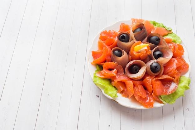Ristorante gourmet che serve un piatto di sale affumicato, filetti di pesce bianco crudo e salmone