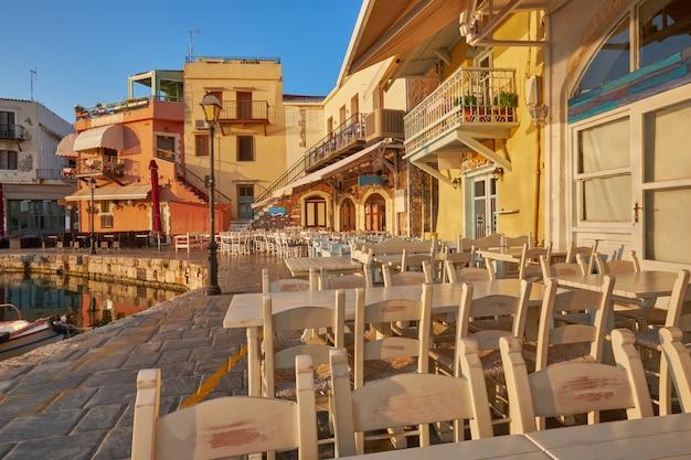Ristorante vuoto sulla banchina del porto storico di rethymno al sole del mattino, tavoli vuoti