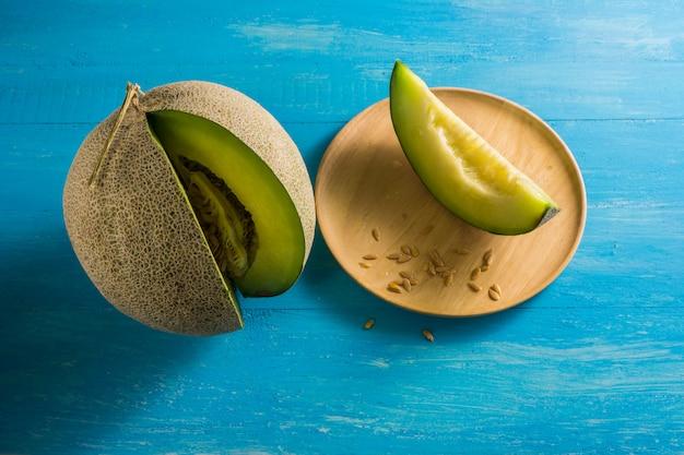 Risultati di melone situato sui tavoli di legno blu e dividere un pezzo