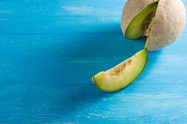 Risultati di melone situato sui tavoli di legno blu e la condivisione esce a pezzi