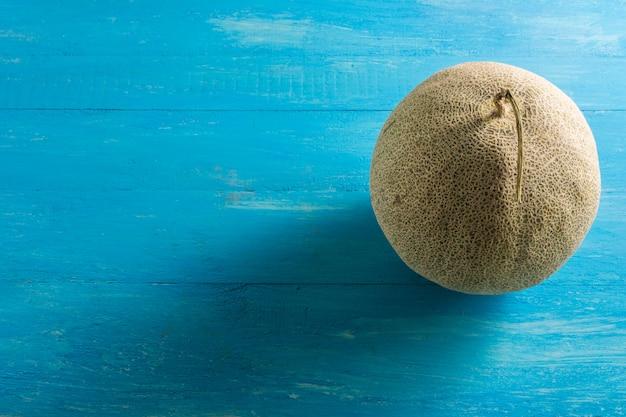 Risultati di melone situato sul tavolo di legno blu
