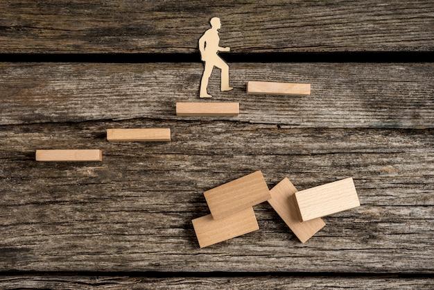 Ritagli di sagoma di un uomo che cammina su gradini in legno con domino sulla vecchia superficie del tavolo in legno grezzo.