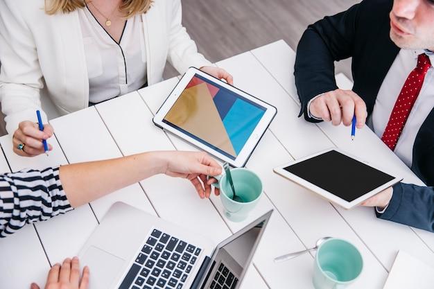 Ritaglia gli uomini d'affari con i gadget alla scrivania
