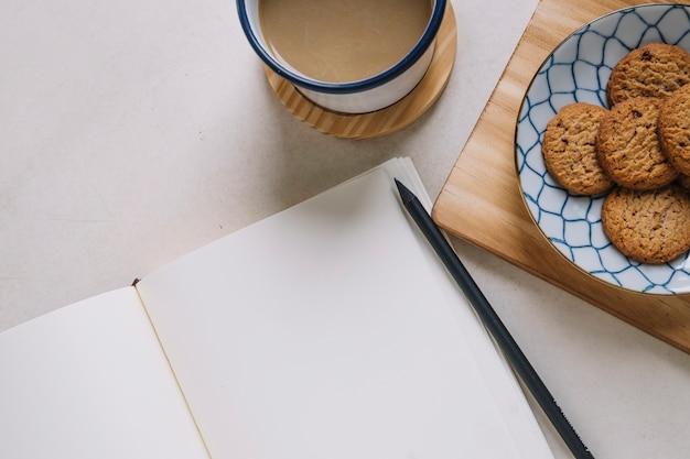 Ritaglia i biscotti e il caffè vicino allo sketchbook