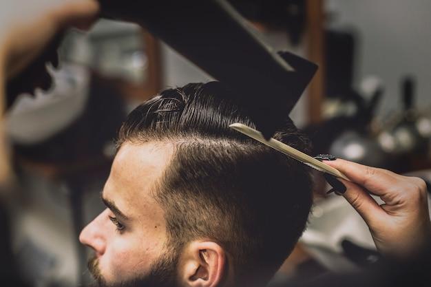Ritaglia il barbiere che asciuga i capelli del cliente