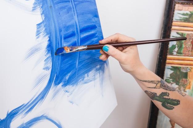 Ritaglia il braccio dell'artista tatuato tenendo il pennello e la pittura