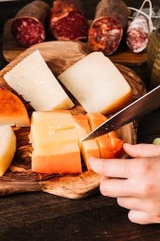 Ritaglia il formaggio per tagliare a mano vicino alle salsicce