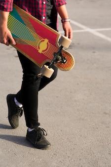 Ritaglia il longboard nelle mani dei pantaloni a vita bassa