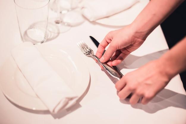 Ritaglia la cameriera che organizza le posate sul tavolo