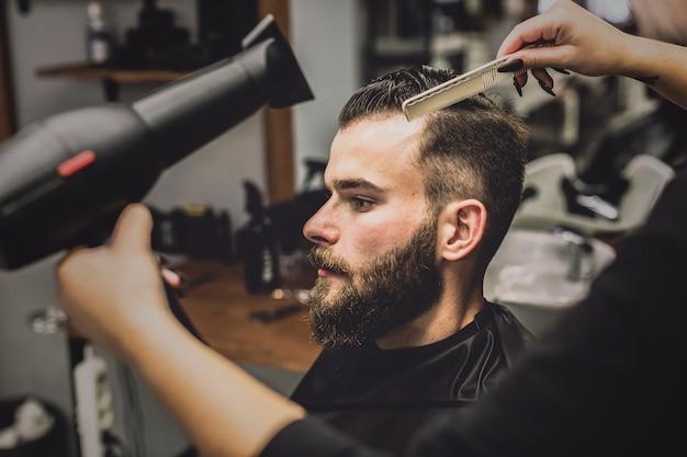 Ritaglia la donna che asciuga i capelli dell'uomo nel negozio di barbiere