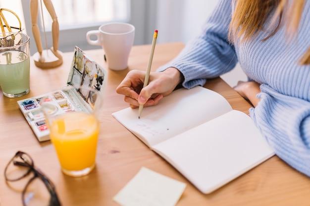 Ritaglia la donna che disegna nello sketchbook