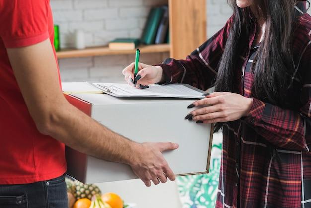 Ritaglia la donna che firma per pacco consegnato