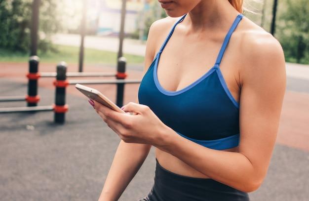 Ritaglia la foto della giovane donna attraente di misura nell'usura di sport che fa l'addestramento con il cellulare sull'area di allenamento della via.