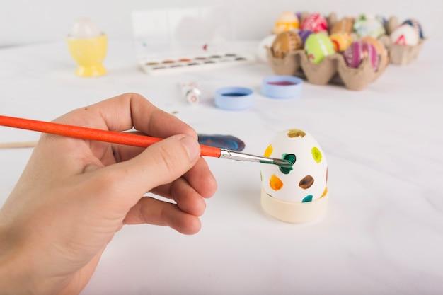 Ritaglia la mano che dipinge l'uovo di pasqua