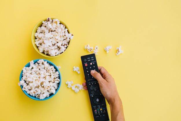 Ritaglia la mano con il telecomando vicino al popcorn