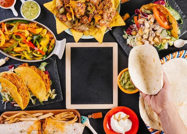 Ritaglia la mano con la tortilla sul cibo messicano