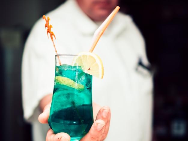 Ritaglia la mano del barista anonimo passando una bevanda rinfrescante