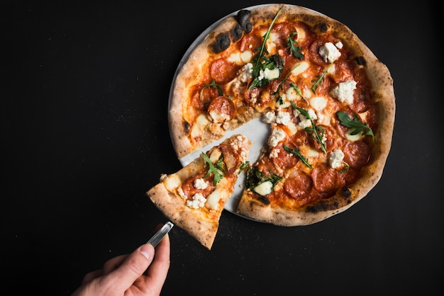 Ritaglia la mano prendendo il pezzo di pizza