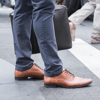 Ritaglia le gambe dell'uomo d'affari vicino alla strada