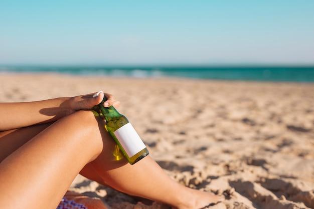 Ritaglia le gambe femminili e la mano con la birra