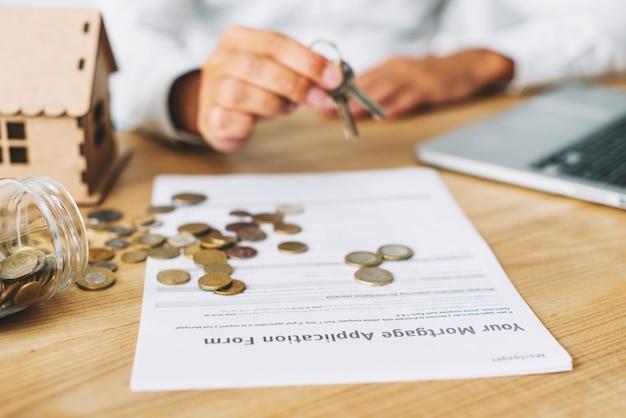 Ritaglia le mani con le chiavi vicino a monete e domanda di mutuo