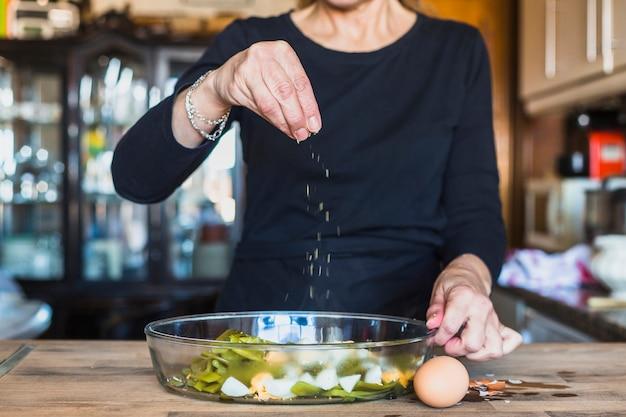 Ritaglia le mani della donna anziana che spruzza il piatto con sale