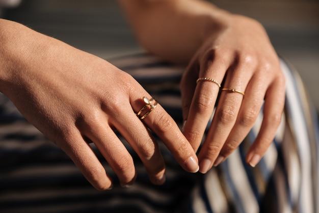 Ritaglia le mani della donna con gli anelli sulla strada